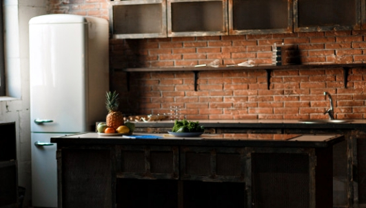cocina-loft-oscuro-pared-ladrillo-rojo-mesa-cocina-cubiertos-cucharas-tenedores-fruta-desayuno_8353-7990